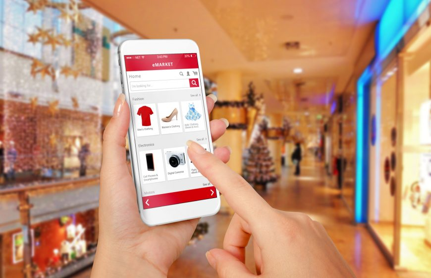 Smart phone online shopping in woman hand during Christmas. Shopping center in background. Buy clothes shoes accessories with e commerce web site