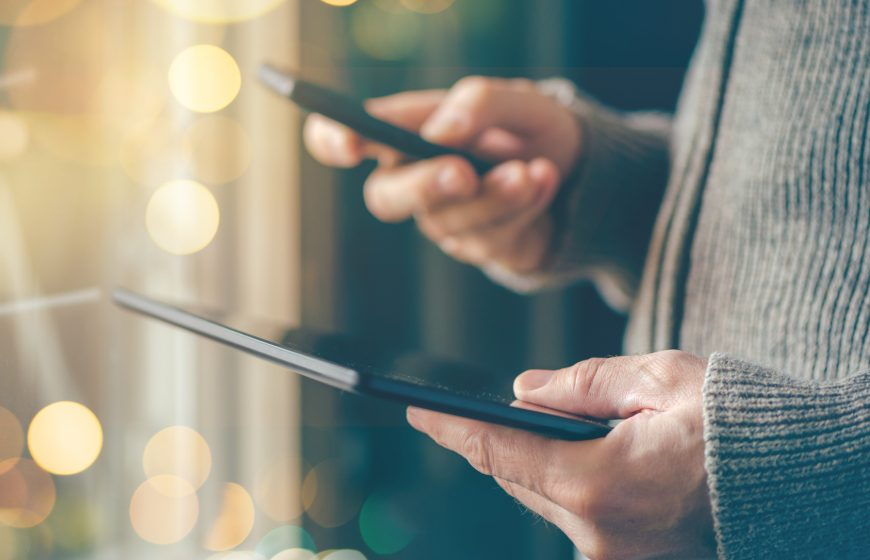 Smartphone and tablet data synchronization, man syncing files and documents on personal wireless electronic devices at home, selective focus with shallow depth of field and bokeh light.